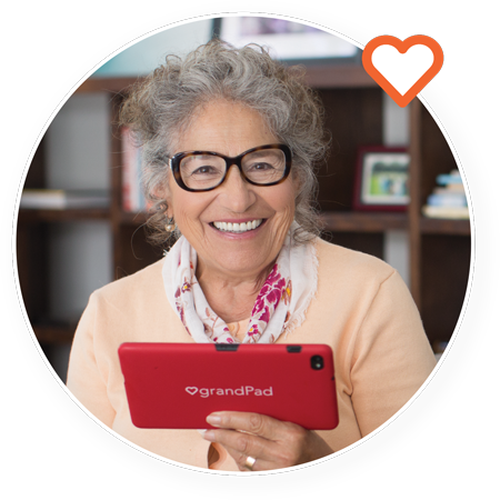 A smiling woman is shown enjoying her GrandPad tablet.